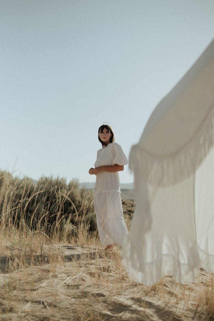 девушка в белом льняном платье стоит на фоне природы