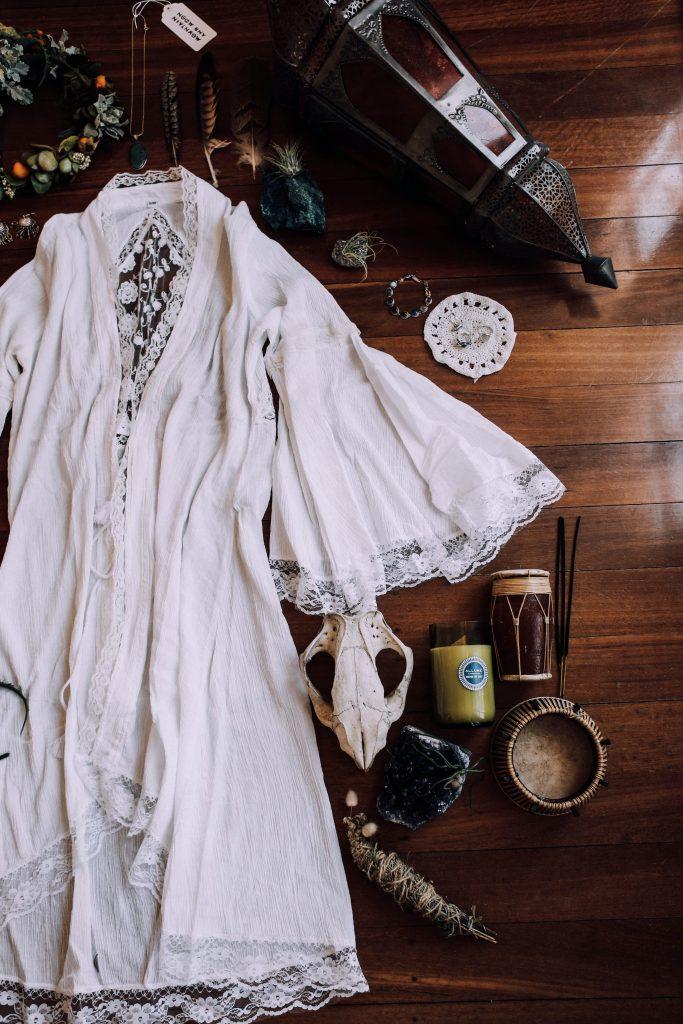 белый льняной летний жакет лежит на фоне деревянного пола