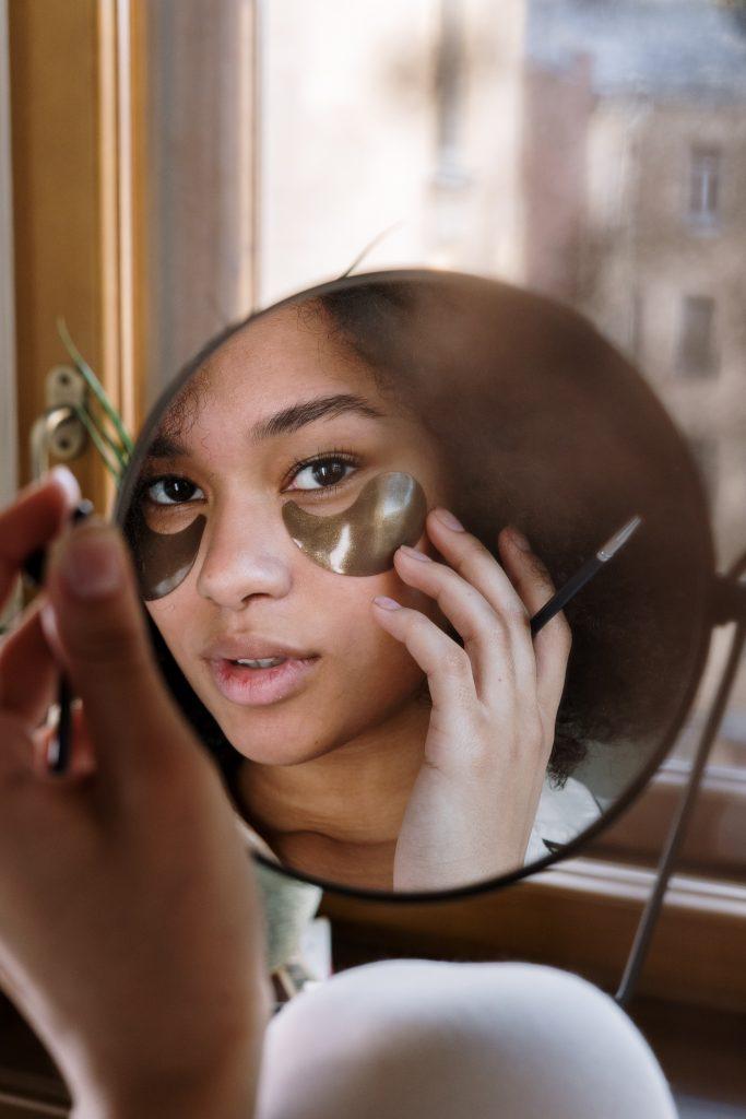 круглое зеркало в котором отражается девушка с патчами на лице