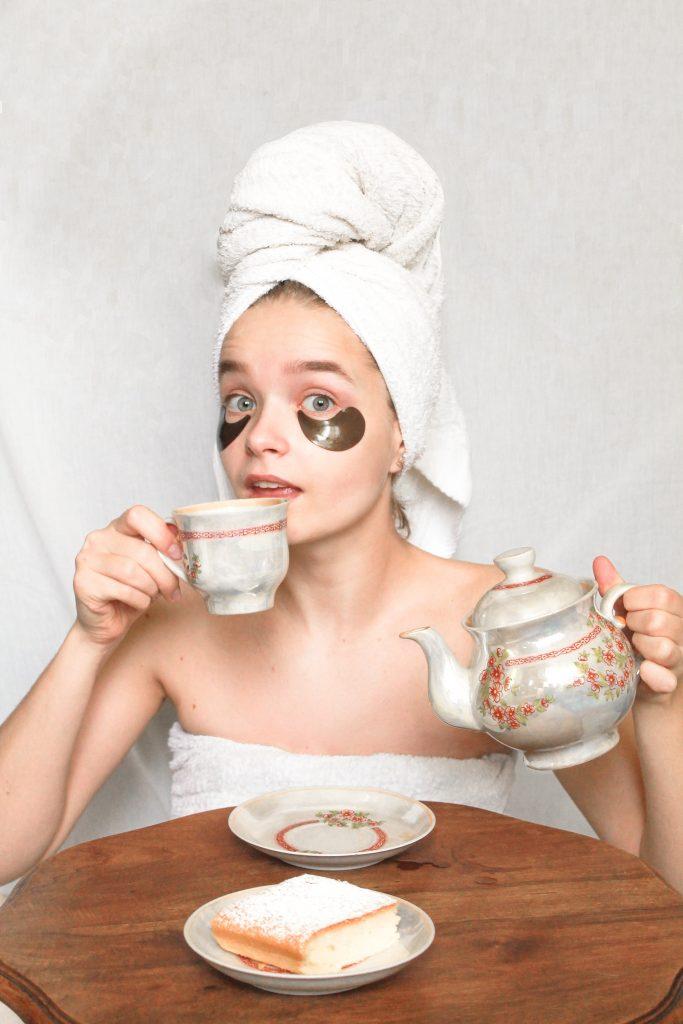 девушка с полотенцем на волосах и патчами на лице пьет чай